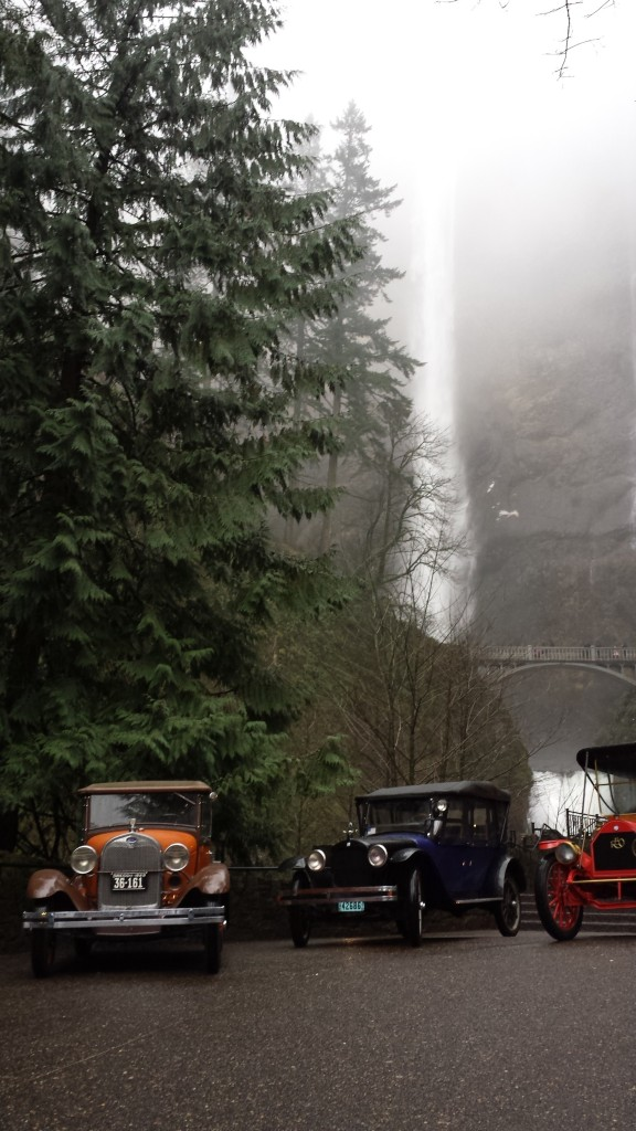 Antique autos parked below Multnomah Falls as they might have in the 1920s.
